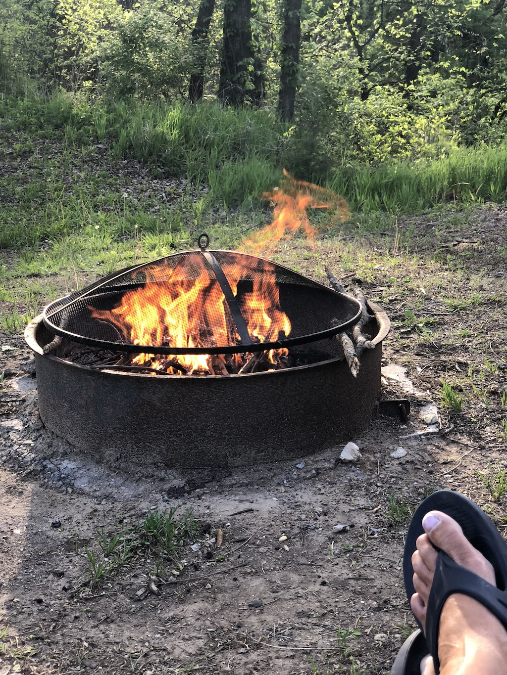 Check out our 6 ways to save money on campsite rentals, so you can sleep under the stars for less. Enjoying an evening by the campfire.
