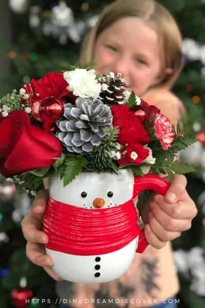 girl holding snowman mug bouquet